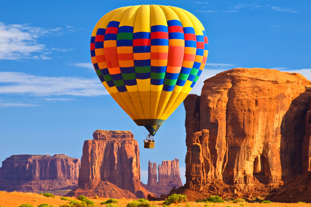 A hot air balloon traverses the rock formations at Monument Valley in northern Arizona.